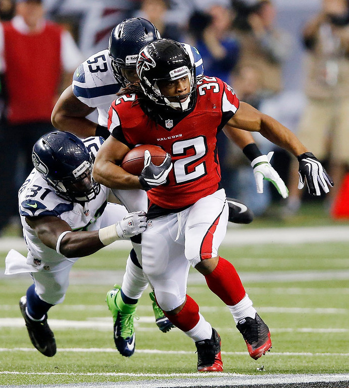Description of . Atlanta Falcons running back Jacquizz Rodgers (32) works against Seattle Seahawks outside linebacker Malcolm Smith (53) and strong safety Kam Chancellor (31) during the second half of an NFC divisional playoff NFL football game Sunday, Jan. 13, 2013, in Atlanta. (AP Photo/John Bazemore)