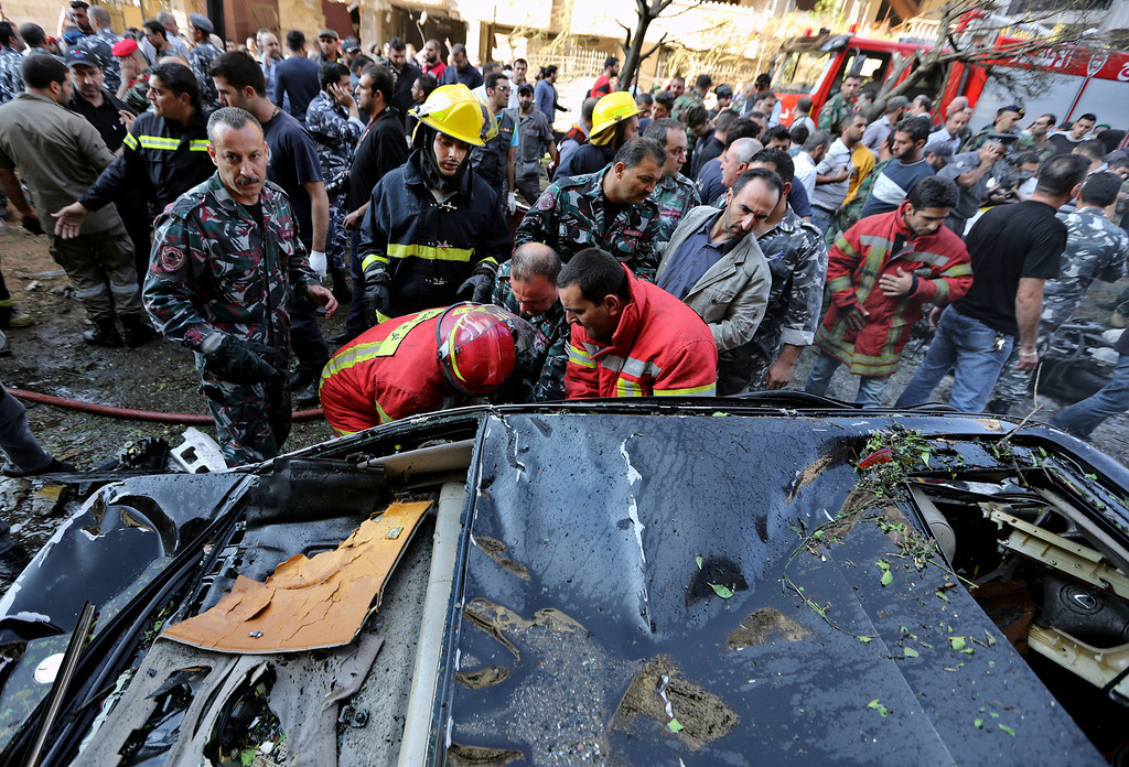 Description of . Lebanese Red Cross workers, pull a body from the inside of a car at the scene where two explosions have struck near the Iranian Embassy killing many, in Beirut, Lebanon, Tuesday, Nov. 19, 2013.  (AP Photo/Bilal Hussein)