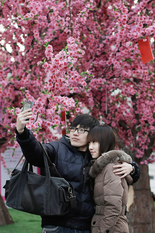 Description of . A couple takes a picture of themselves on Valentine's Day February 14, 2013 in Beijing, China. Young Chinese couples have embraced the Western concept of Valentine's Day with hawkers selling roses and chocolates.(Photo by Lintao Zhang/Getty Images)