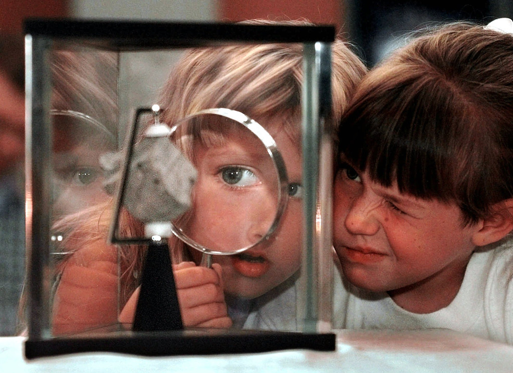 Description of . Six-year-olds Amanda Johanson, left, and Camille Baer share a magnifiying glass while inspecting  a Martian meteorite on display at the New Mexico Museum of Natural History and Science in Albuquerque, N.M., Sunday, July13, 1997. The meteorite is one of only 12 meteorites world-wide that has been identified as originating from Mars. (AP Photo/Eric Draper)