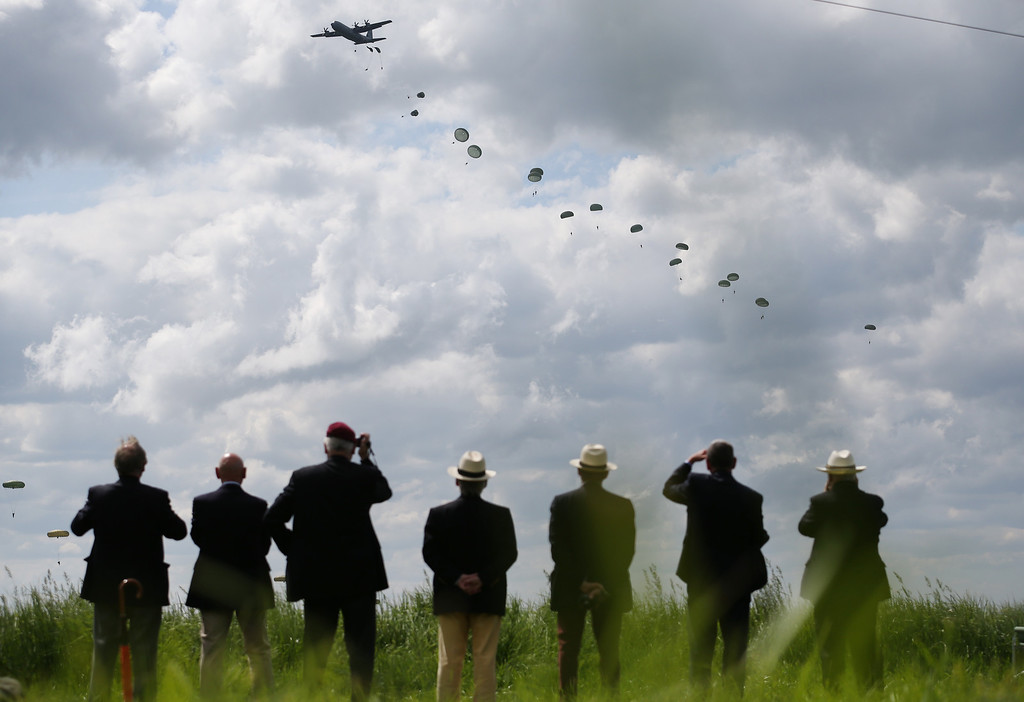 Description of . People watch as a parachute drop takes place on June 5, 2014 near Ranville, France.   (Photo by Peter Macdiarmid/Getty Images)