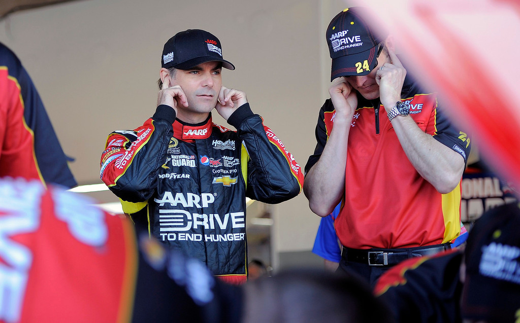 . NASCAR Sprint Cup Series driver Jeff Gordon (L), of the number 24 car, plugs his ears with a crew member as a car starts in the garage during practice for the Daytona 500 at Daytona International Speedway in Daytona Beach, Florida, February 20, 2013. REUTERS/Brian Blanco