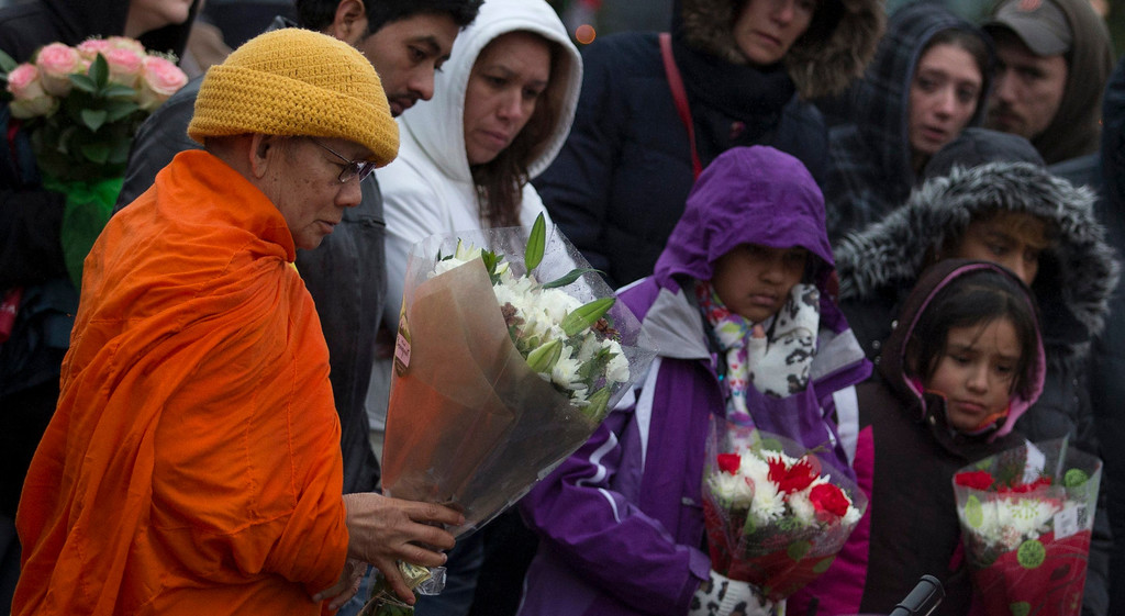 Description of . A Buddhist monk from Thailand leaves flowers for victims of the Sandy Hook Elementary shooting at a memorial in Sandy Hook Village in Newtown, Connecticut December 16, 2012. Worshippers filled Sunday services to mourn the victims of a gunman's elementary school rampage that killed 20 children and six adults with President Barack Obama due to appear later at an interfaith vigil to help this shattered Connecticut town recover.   REUTERS/Adrees Latif