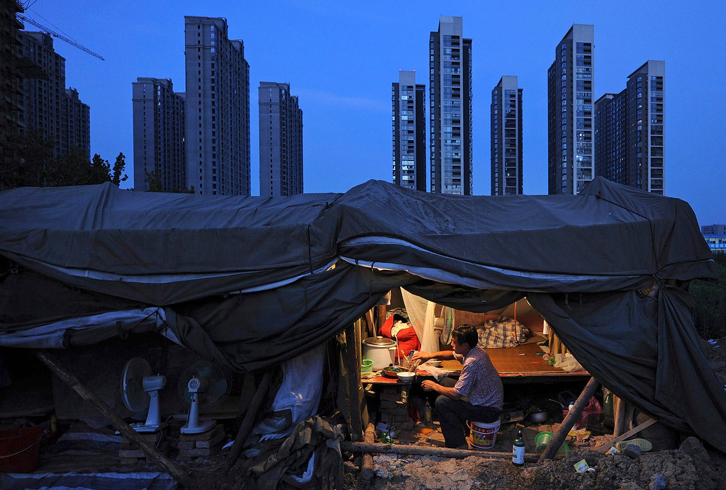 Description of . A laborer has his dinner under his shed at a construction site of a residential complex in Hefei, Anhui province, August 1, 2012. The average home price in China's 100 major cities edged up in July for the second straight month, reinforcing signs of a recovery in the property market even as the government seeks to spur broader economic growth, a private sector survey showed on Wednesday. Picture taken August 1, 2012. REUTERS/Stringer
