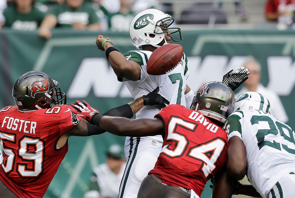 Description of . New York Jets quarterback Geno Smith, center, gets the ball knocked out of his hands by Tampa Bay Buccaneers middle linebacker Mason Foster (59) in the first half of an NFL football game, Sunday, Sept. 8, 2013, in East Rutherford, N.J. Tampa Bay Buccaneers' Lavonte David (54) and New York Jets' Bilal Powell (29) try to help their respective teammate during the play. The Buccaneers recovered the fumble. (AP Photo/Mel Evans)