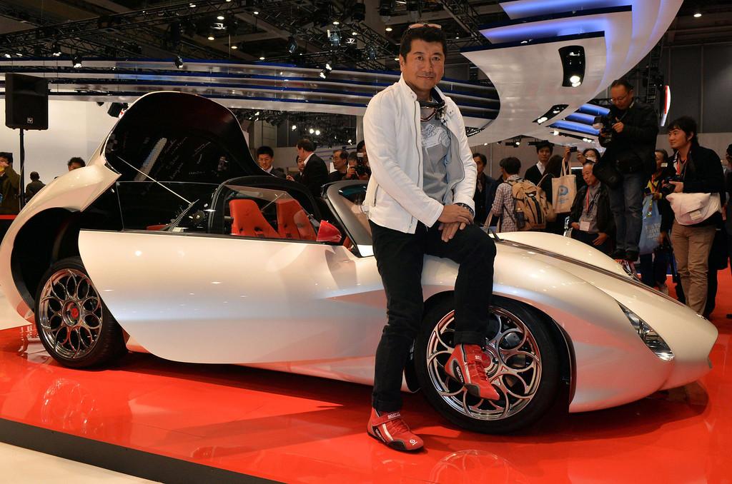 Description of . Japanese car designer Ken Okuyama, who designed a Ferrari car, displays the new lightweight sports car