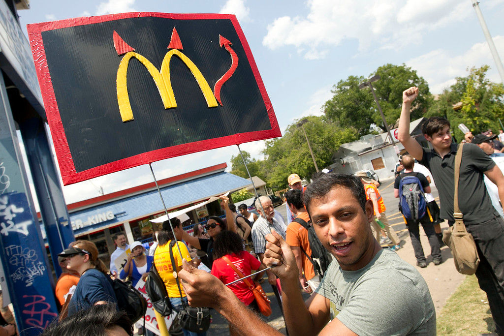 Description of . Danny Alvarez protests at a Burger King fast food restaurant in Austin,Texas on Thursday Aug. 29, 2013. Fast-food protests were under way Thursday in U.S. cities including New York, Chicago and Detroit, with organizers expecting the biggest national walkouts yet in a demand for higher wages.  (AP Photo/Austin American-Statesman, Jay Janner)