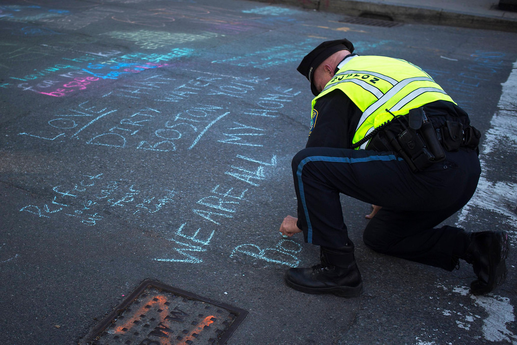 Description of . Boston police officer Pat Duggan writes in chalk outside a makeshift memorial along Newbury street in Boston, Massachusetts April 17, 2013. The investigation of the Boston Marathon bombing is focusing on a suspect or suspects believed to have carried heavy bags or backpacks, but entered a third day on Wednesday without any arrests or word on who was responsible. REUTERS/Shannon Stapleton
