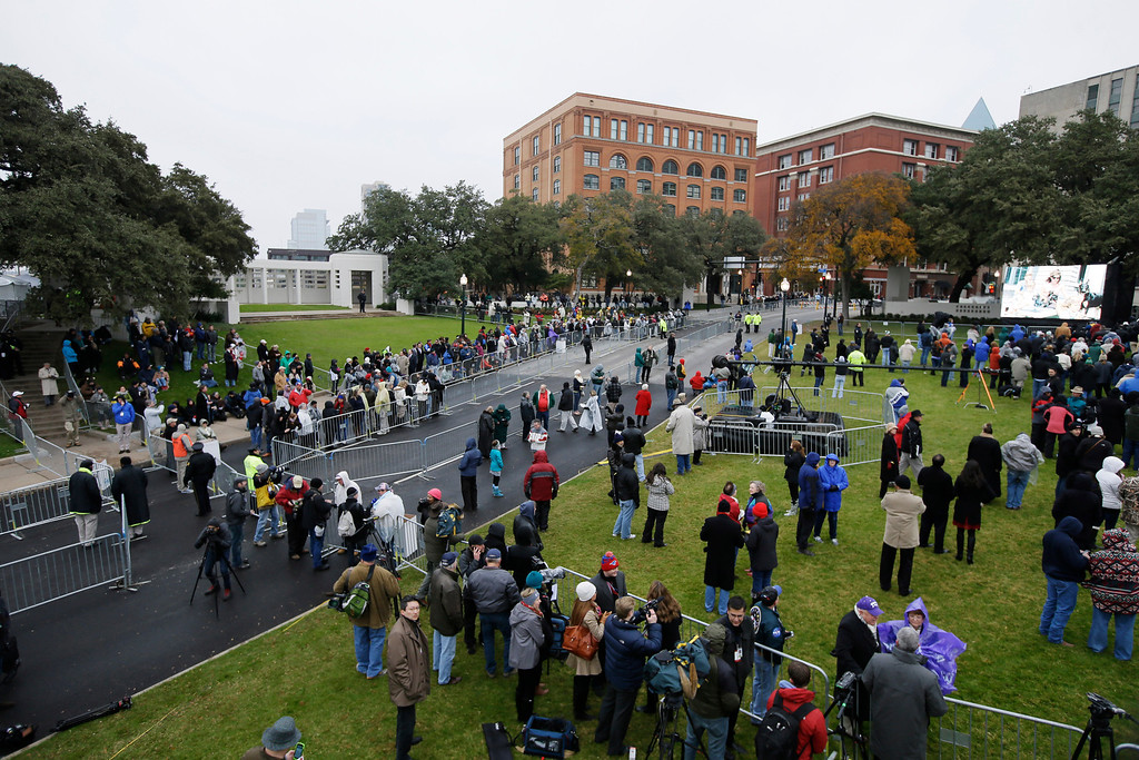 Description of . A crowd moves into position before a ceremony to mark the 50th anniversary of the assassination of John F. Kennedy, Friday, Nov. 22, 2013, at Dealey Plaza in Dallas. President Kennedy's motorcade was passing through Dealey Plaza when shots rang out on Nov. 22, 1963. (AP Photo/Tony Gutierrez)