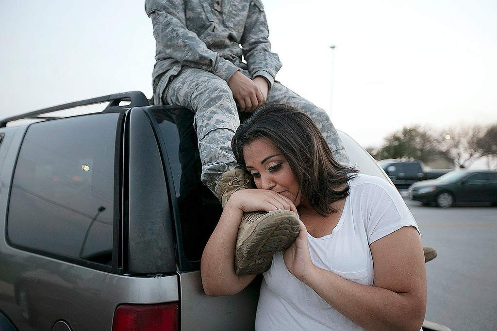 Description of . Lucy Hamlin leans on her husband's foot, Specialist Timothy Hamlin, as they wait to be allowed back onto Fort Hood, Texas, where they reside on Wednesday, April 2, 2014. A shooting occurred on the base with at least four dead and 14 injured according to the officials. (AP Photo/Austin American-Statesman, Deborah Cannon)