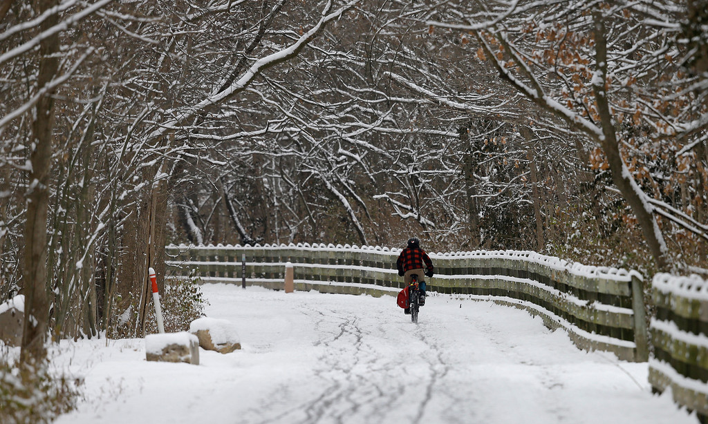 Description of . A bicyclist rides his bike on the Monon Trail following a winter storm Friday, Dec. 6, 2013, in Indianapolis. Several inches of snow fell on central and southern Indiana, making driving treacherous and leading to at least two fatal crashes. (AP Photo/Darron Cummings)