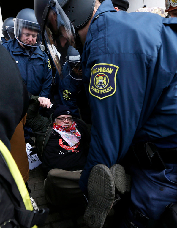 Description of . Michigan State Police carry a protester from a rally at the George W. Romney State Building, where Gov. Snyder has an office in Lansing, Mich., Tuesday, Dec. 11, 2012. The crowd is protesting right-to-work legislation passed last week. Michigan could become the 24th state with a right-to-work law next week. Rules required a five-day wait before the House and Senate vote on each other's bills; lawmakers are scheduled to reconvene Tuesday and Gov. Snyder has pledged to sign the bills into law. (AP Photo/Paul Sancya)