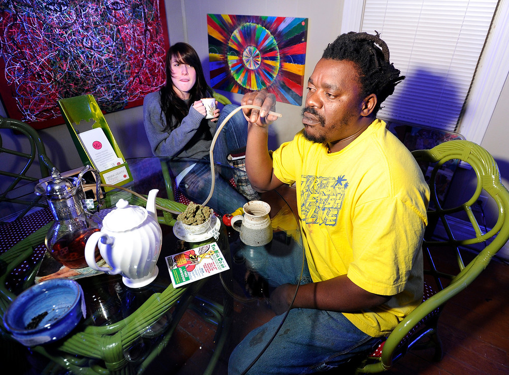 Description of . Bongo Love, of Lafayette, takes a hit of marijuana from a vaporizer while sitting next to Kyrie Wozab, of Louisville, on Wednesday, Jan. 2, at The Hive Co-Op Cannabis Club in Lafayette. Jeremy Papasso/Boulder Daily Camera