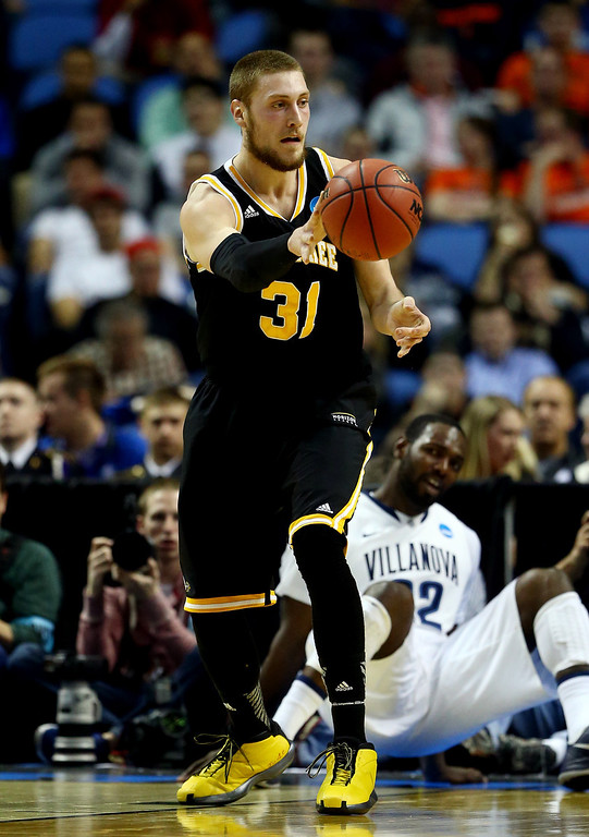 Description of . BUFFALO, NY - MARCH 20: Matt Tiby #31 of the Milwaukee Panthers passes the ball against the Villanova Wildcats during the second round of the 2014 NCAA Men's Basketball Tournament at the First Niagara Center on March 20, 2014 in Buffalo, New York.  (Photo by Elsa/Getty Images)