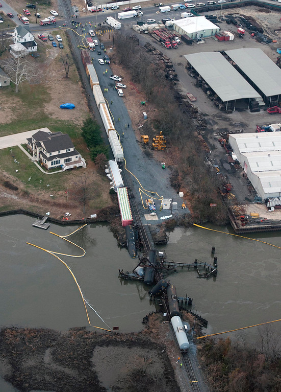 . Several cars lay in the water after a freight train derailed in Paulsboro, N.J., Friday, Nov. 30, 2012. People in three southern New Jersey towns were told Friday to stay inside after the freight train derailed and several tanker cars carrying hazardous materials toppled from a bridge and into a creek. (AP Photo/Cliff Owen)