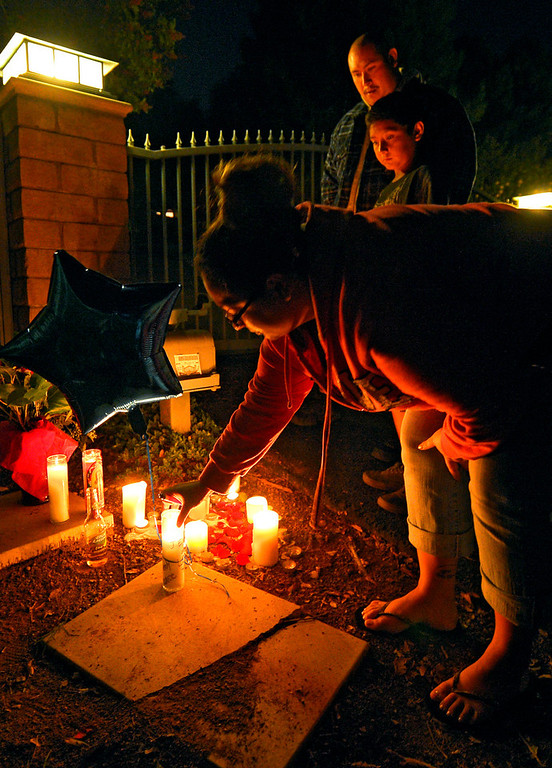 Description of . Cecy Robles places candle and a balloon in front of what is believed to be the home of singer Jenni Rivera as Ruben Robles, top, and Anthony Robles watch on Sunday, Dec. 9, 2012, in the Encino section of Los Angeles. The wreckage of a small plane believed to be carrying Rivera, the U.S-born singer whose soulful voice and unfettered discussion of a series of personal travails made her a Mexican-American superstar, was found in northern Mexico on Sunday. Authorities said there were no survivors. (AP Photo/Mark J. Terrill)