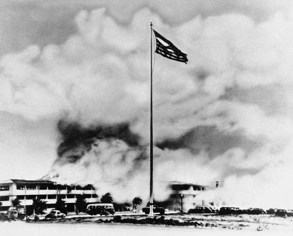 Description of . In this photo provided by the U.S. Air Force, while buildings (background) burn after being struck by Japanese bombs, the American flag, though torn, still flew above Hickam Field, during the height of the sneak attack, Dec. 7, 1941. (AP Photo/USAF)