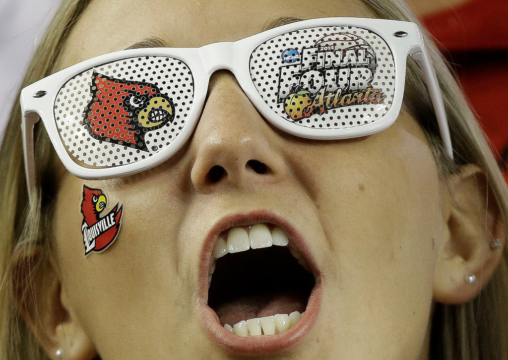 Description of . A Louisville fan cheers before the first half of the NCAA Final Four tournament college basketball championship game against the Michigan, Monday, April 8, 2013, in Atlanta. (AP Photo/David J. Phillip)