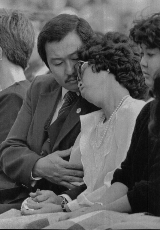 Description of . Claude Onizuke, brother of astronaut Elison Onizuka, comforts the astronaut\'s widow Lorna Onizuka during a memorial for the seven dead astronauts on Jan. 31, 1986 at the Johnson Space Center is Houston.  Daughter of the astronaut Janelle Onizuka, sits on the right.  Denver Post Library Archive