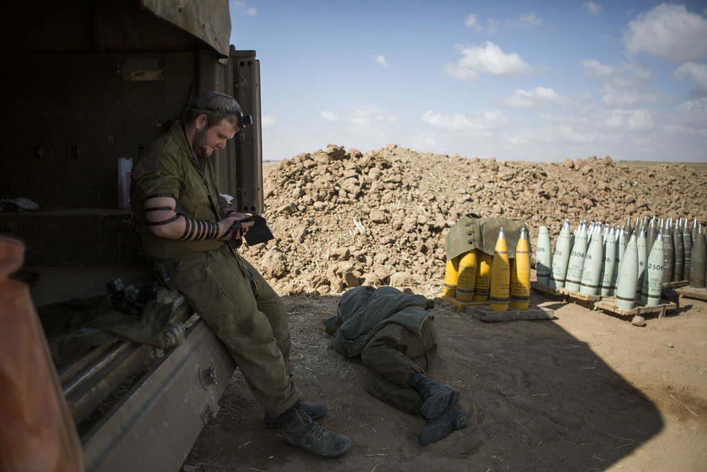 Description of . Israeli soldier seen praying by artillery cannon on July 16, 2014 at the Israeli-Gaza border. An Egyptian ceasefire proposal was yesterday refused by Hamas, who continued their missile bombardment on Israel. Israel has today issued a warning to 100,00 residents of northern Gaza to evacuate their homes as it continues with planned airstrikes as part of operation 'Protective Edge'. Israeli Prime Minister Benjamin Netanyahu said he had