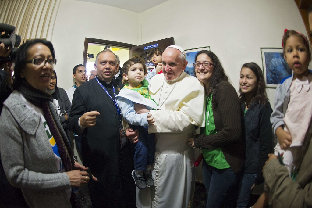 Description of . Pope Francis holds a baby as he meets the residents of the Varginha favela in Rio de Janeiro, Brazil on July 25, 2013. The Varginha favela is a community of 1,000 people which for decades was under the sway of narco-traffickers until it came under police control less than a year ago. The first Latin American and Jesuit pontiff arrived in Brazil mainly for the huge five-day Catholic gathering World Youth Day.  OSSERVATORE ROMANO/AFP/Getty Images