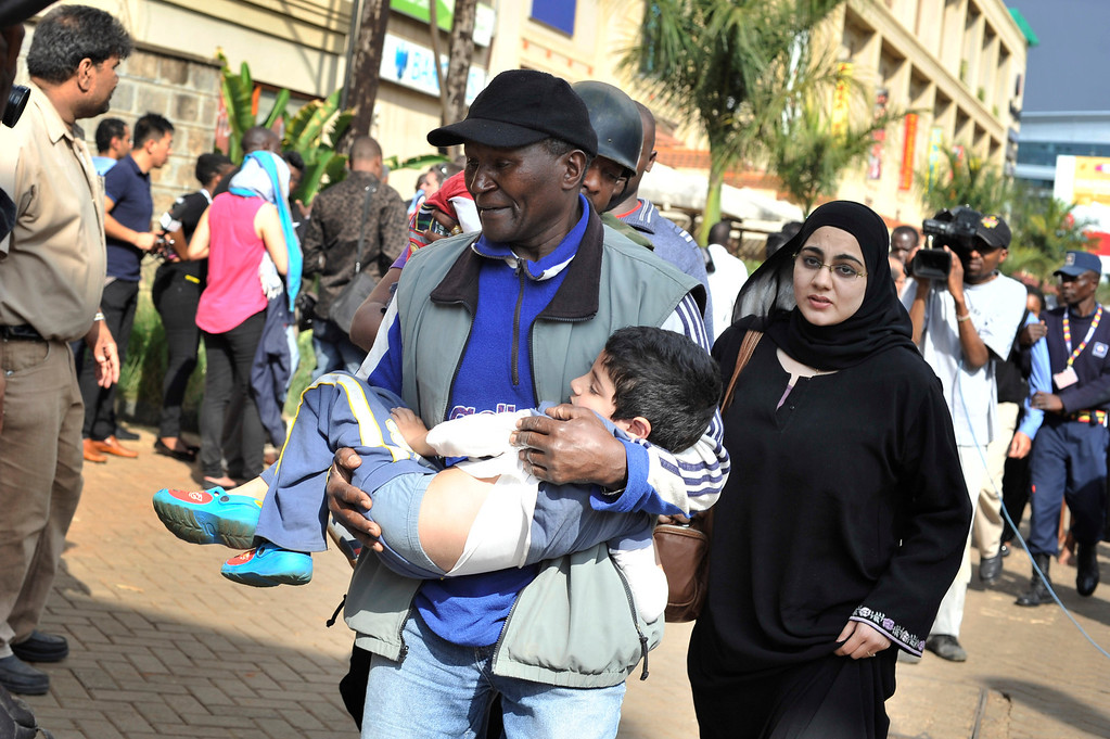Description of . A rescue worker helps a child outside the Westgate Mall in Nairobi, Kenya Saturday, Sept. 21, 2013, after gunmen threw grenades and opened fire during an attack that left multiple dead and dozens wounded.  (AP Photo/Riccardo Gangale)