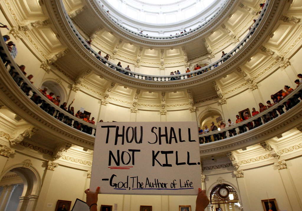 Description of . An anti-abortion protester holds a placard as protesters line the railing on the second floor of the rotunda of the State Capitol as the state Senate meets to consider legislation restricting abortion rights in Austin, Texas July 12, 2013. Texas on Friday is poised to enact a ban on most abortions after 20 weeks of pregnancy, ending a bitter political fight that stirred national debate over what critics see as laws threatening the right to abortion in the United States. REUTERS/Mike Stone