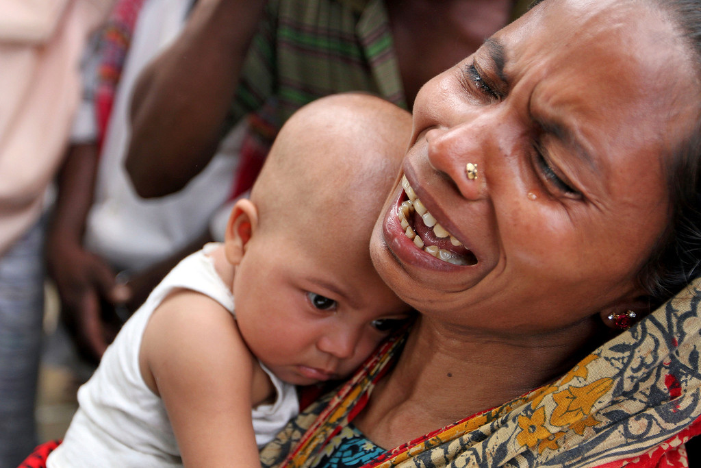 Description of . A Bangladeshi woman holds her daughter and weeps as Bangladeshi people hold photographs of their relatives whom they believe are trapped in the rubble of a building that collapsed in Savar, outskirts of Dhaka, Bangladesh, Tuesday, April 30, 2013. (AP Photo/Palash Khan)