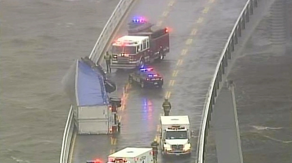 Description of . In this image from video provided by WJZ-TV, emergency crews surround a tractor-trailer that overturned on the westbound span of the Bay Bridge, which crosses the Chesapeake Bay in Maryland. The bridge was closed in both directions after the crash Wednesday afternoon due to high winds from a snowstorm blowing through the Mid-Atlantic region. (AP Photo/WJZ-TV)