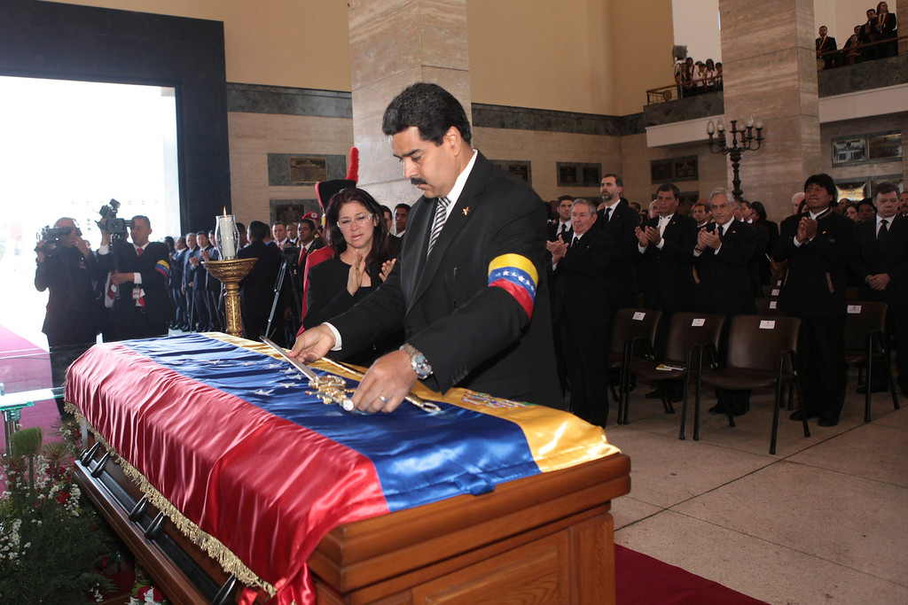 Description of . Venezuelan Vice-President Nicolas Maduro lays a replica of the Simon Bolivar's sword on the coffin of Venezuela's late President Hugo Chavez at the Military Academy in Caracas March 8, 2013, in this picture provided by the Miraflores Palace.  REUTERS/Miraflores Palace/Handout