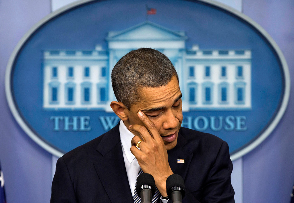 Description of . President Barack Obama wipes his eye as he talks about the Connecticut elementary school shooting, Friday, Dec. 14, 2012, in the White House briefing room in Washington. (AP Photo/Carolyn Kaster)