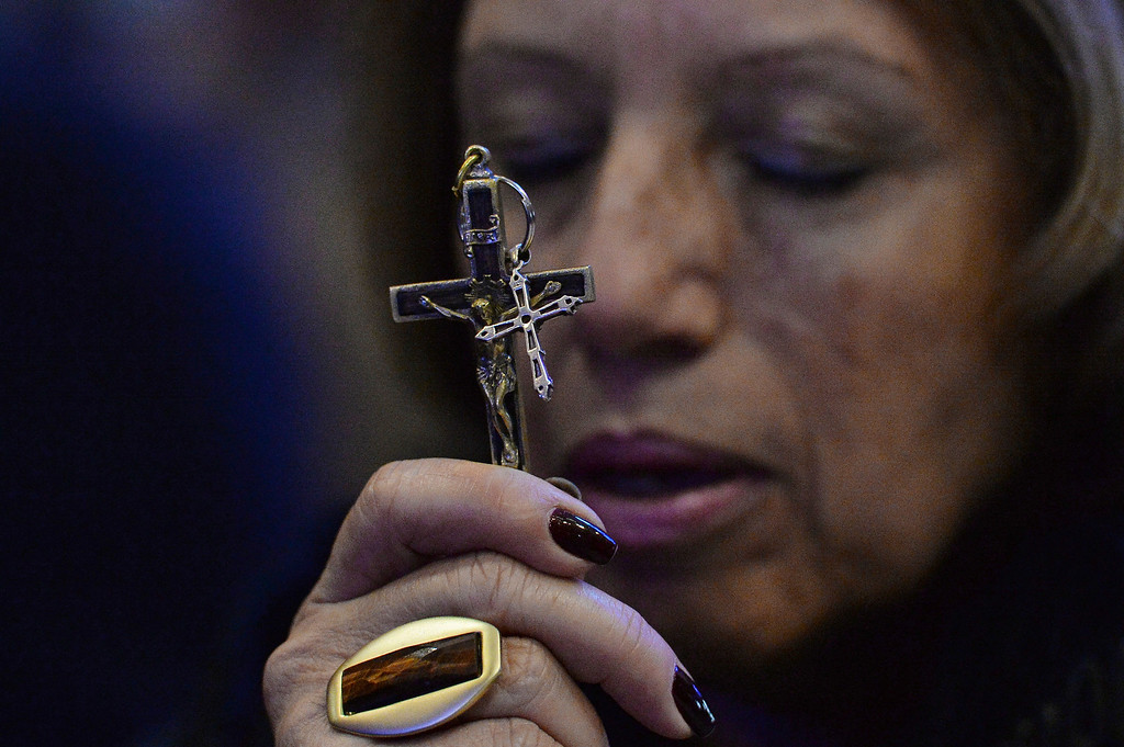 Description of . A woman prays as she holds two crucifixes while waiting for the arrival of Pope Francis to the Aparecida basilica in Aparecida, Brazil, Wednesday, July 24, 2013. Tens of thousands of faithful flocked to the tiny town of Aparecida, tucked into an agricultural region halfway between Rio de Janeiro and Sao Paulo, where Francis celebrated the first public Mass of his trip in the basilica dedicated to the nation's patron saint. (AP Photo/Luca Zennaro, Pool)
