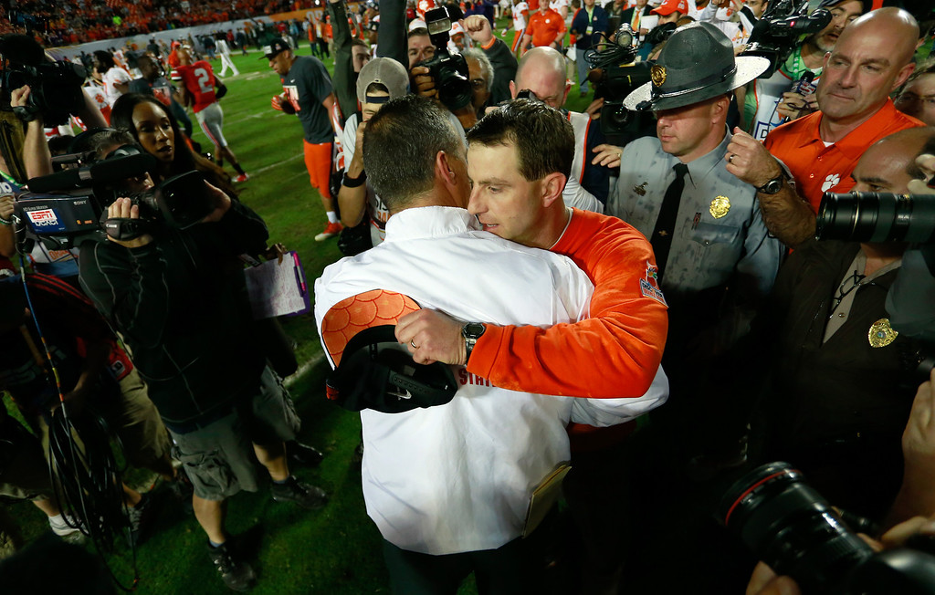 Description of . MIAMI GARDENS, FL - JANUARY 03:  Head coach Dabo Swinney of the Clemson Tigers and head coach Urban Meyer of the Ohio State Buckeyes shake hands after the the Discover Orange Bowl at Sun Life Stadium on January 3, 2014 in Miami Gardens, Florida. Clemson defeated Ohio State 40-35.  (Photo by Chris Trotman/Getty Images)