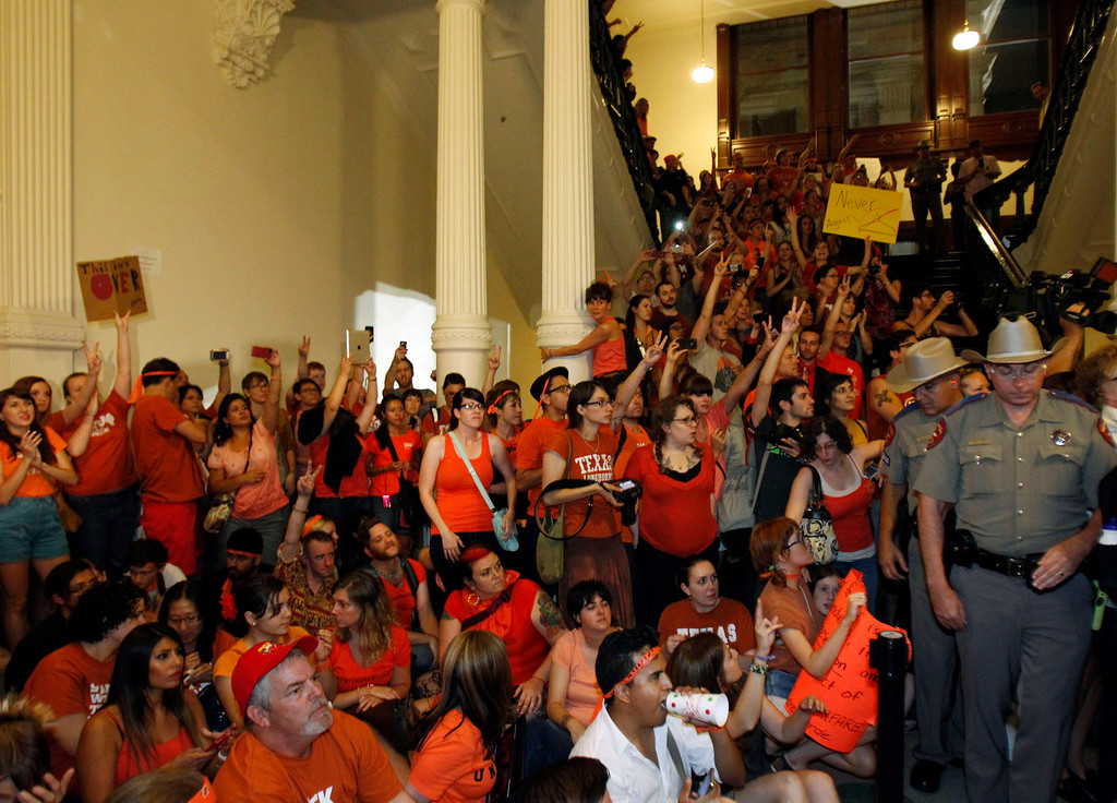 Description of . Abortion rights protesters rally inside the State Capitol after the state Senate passed legislation restricting abortion rights in Austin, Texas, July 13, 2013.  The Republican-controlled Texas Senate passed a bill to ban most abortions after 20 weeks of pregnancy, ending a political battle that stirred national debate over what critics see as laws threatening the right to abortion in the United States. REUTERS/Mike Stone