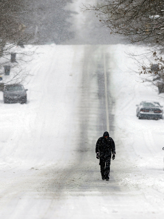 Description of . A pedestrian makes his way down a snow-covered street as snow continues to fall in Indianapolis, Thursday, Jan. 2, 2014. Over 5 inches of snow fell in Central Indiana. (AP Photo/Michael Conroy)