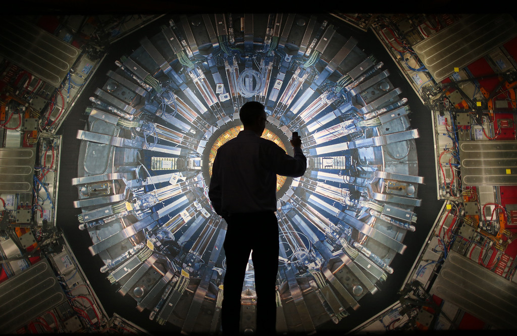 Description of . A visitor takes a phone photograph of a large back lit image of the Large Hadron Collider (LHC) at the  Science Museum's 'Collider' exhibition on November 12, 2013 in London, England.  (Photo by Peter Macdiarmid/Getty Images)