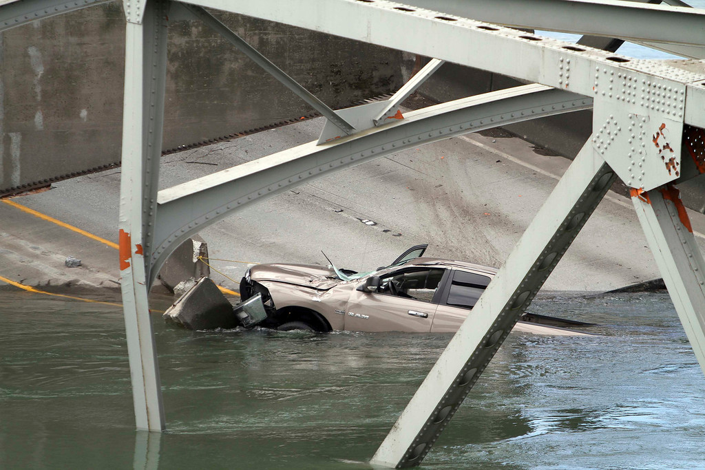 Description of . A car is seen in the water as a span of highway bridge sits in the Skagit River May 24, 2013 after collapsing near the town of Mt Vernon, Washington late Thursday. The bridge collapse that sent cars and drivers tumbling into a frigid river in Washington state appears to have been caused when a semi-trailer truck carrying an oversize load struck a bridge support beam, officials said on Friday. The truck crossed the bridge safely before a portion of the structure collapsed, sending two vehicles and a mass of concrete and steel into the Skagit River Thursday evening. Three people had to be rescued, officials said.   REUTERS/Cliff DesPeaux