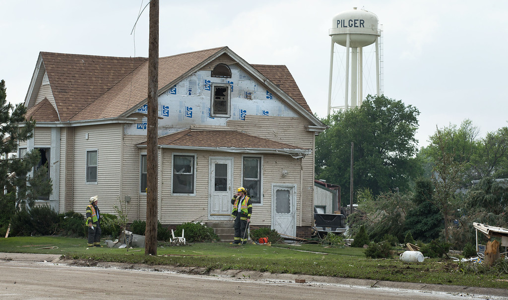 . Firefighters go door to door and check homes for people after a tornado struck in Pilger, Neb., Monday, June 16, 2014. The National Weather Service said at least two twisters touched down within roughly a mile of each other. (AP Photo/The World-Herald, Ryan Soderlin)