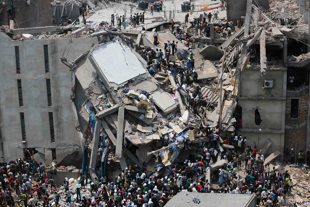 Description of . People rescue garment workers trapped under rubble at the Rana Plaza building after it collapsed, in Savar, 30 km (19 miles) outside Dhaka April 24, 2013. REUTERS/Andrew Biraj