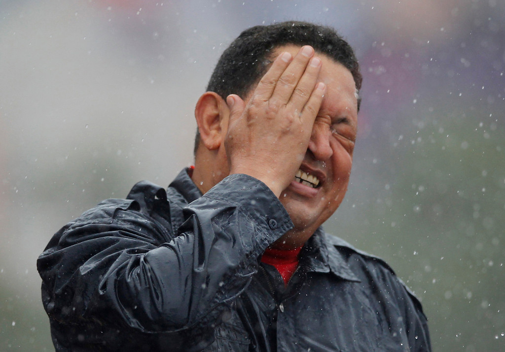 Description of . Venezuela's President and presidential candidate Hugo Chavez wipes his face under the rain during his closing campaign rally in Caracas October 4, 2012. REUTERS/Tomas Bravo