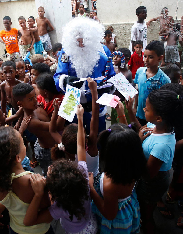 Description of . A policeman of the Peacekeeping Police Unit (UPP) dressed up as Santa Claus in Rio de Janeiro's military police colours, plays with children during a Christmas party at Macacos slum in Rio de Janeiro December 20, 2012. REUTERS/Ricardo Moraes