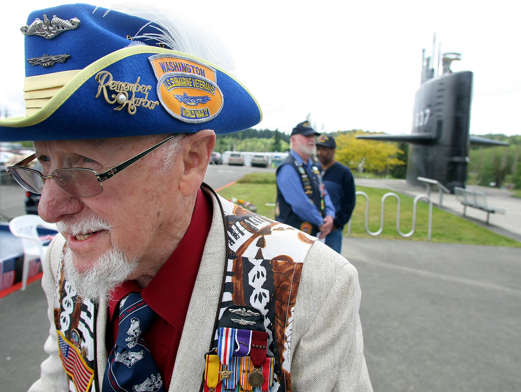 Description of . Ed Ferris of Port Ludlow stand outside Thursday after attending a ceremony at the Naval Undersea Museum Auditorium in Keyport. He was participating in the Tolling the Boats Memorial Day Observance. Ferris served in the U.S. Navy from 1942-67, and was the recipient of the silver star, and four purple hearts. He was on the USS Drum in World war II, and finished serving on a swift boat during the Vietnam conflict. His hat is from severing in Australia during World War II. The event was to honor fallen submarine sailors. (AP Photo/Kitsap Sun, Larry Steagall)