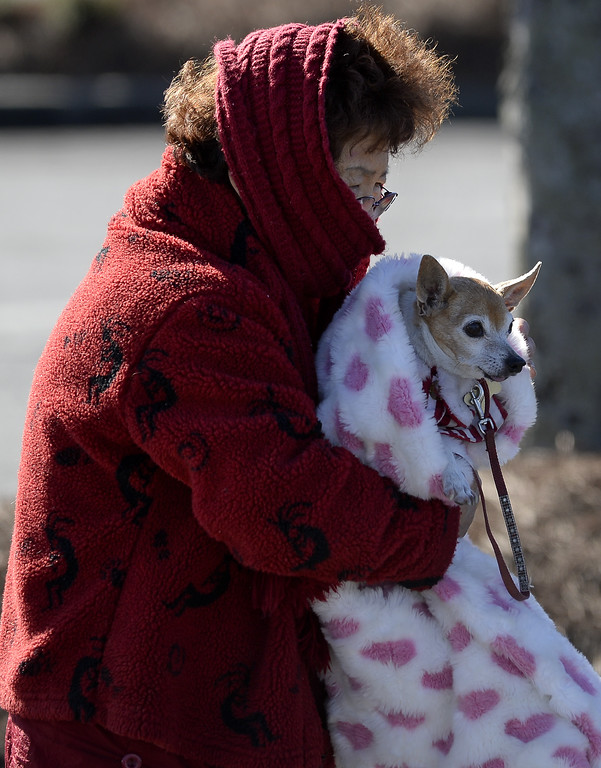 . Doc Cheng bundles up with her chihuahua Happy as she braves  a cold Arctic blast that brought temperatures down to 6 degrees above zero, closing local schools and shattering cold weather records, on Tuesday, Jan. 7, 2014, in Atlanta. (AP Photo/David Tulis)