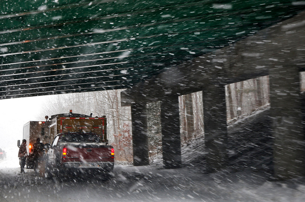Description of . A salt and sand road crew regroups under a bridge as snow falls in Andover, Mass. Thursday, Jan. 2, 2014. Up to 14 inches of snow is forecast for the Boston area. (AP Photo/Elise Amendola)