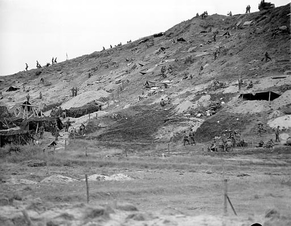 Description of . Allied forces camp out in fox holes, caves and tents on this hillside overlooking the beach at Normandy, France, during the D-Day invasion in World War II.  (AP Photo/Bede Irvin)