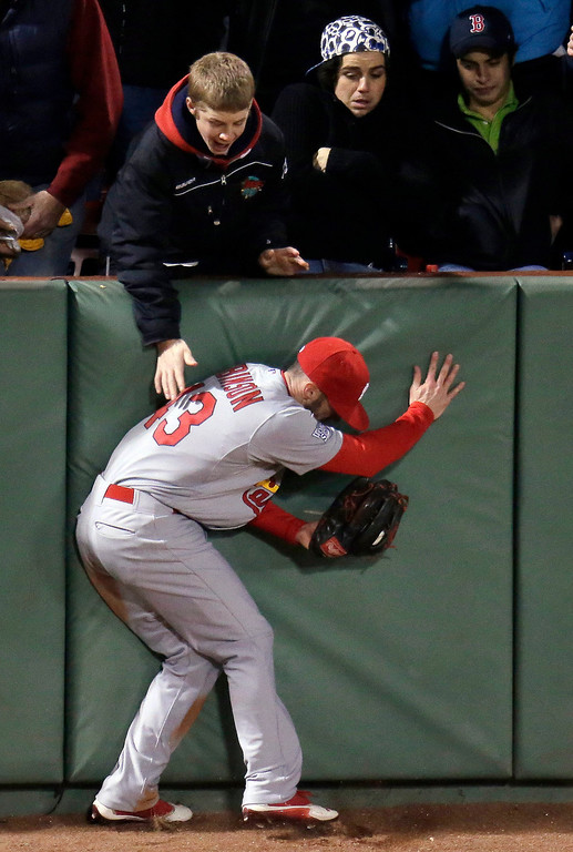 Description of . St. Louis Cardinals' Shane Robinson runs into the wall after catching a ball hit by Boston Red Sox's Dustin Pedroia during the fifth inning of Game 1 of baseball's World Series Wednesday, Oct. 23, 2013, in Boston. (AP Photo/Charlie Riedel)