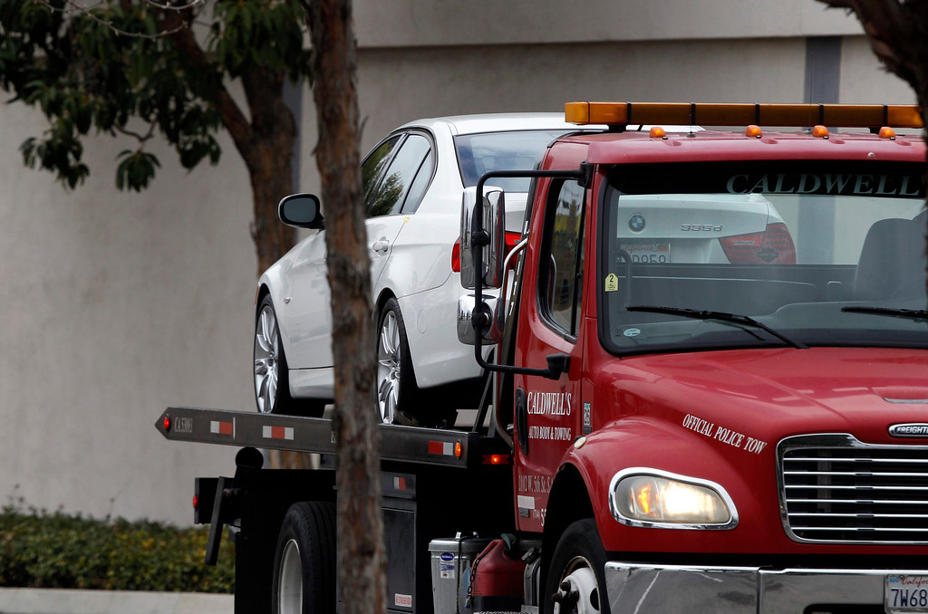 . A white car, which is believed to be stolen, is towed away from the parking lot of a Tustin computer store after a gunman went on a shooting spree in suburban southern California  February 19, 2013. REUTERS/Alex Gallardo