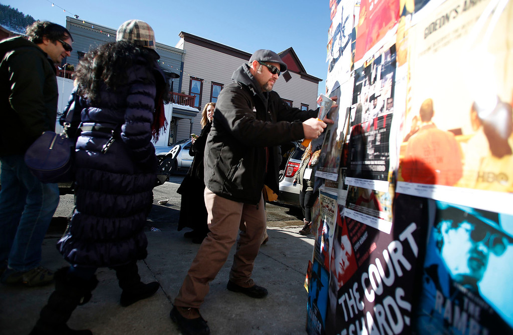 Description of . Mike Christensen puts up movie posters along Main Street during the Sundance Film Festival in Park City, Utah, January 18, 2013.  REUTERS/Jim Urquhart