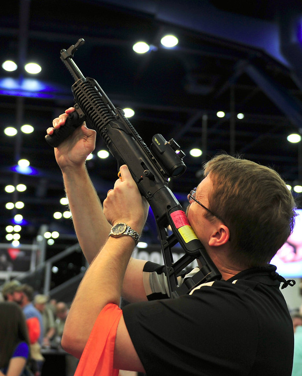 Description of . A man hefts a Hi-Point semi-automatic carbine at the National Rifle Association (NRA) annual Convention annual on May 4, 2013 in Houston, Texas. The National Rifle Association opened its annual convention Friday in combative style, positioning itself as champion of American freedoms in the face of growing pressure for tougher gun laws.  KAREN BLEIER/AFP/Getty Images
