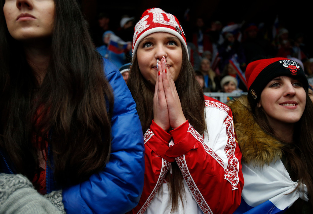 Description of . A Russian fan watches Russia-2 head down the track for Heat 4 of the Two-man Bobsleigh at the Sliding Center Sanki for the 2014 Winter Olympics in Krasnaya Polyana, Russia on Monday, Feb. 17, 2014.  (Nhat V. Meyer/Bay Area News Group)